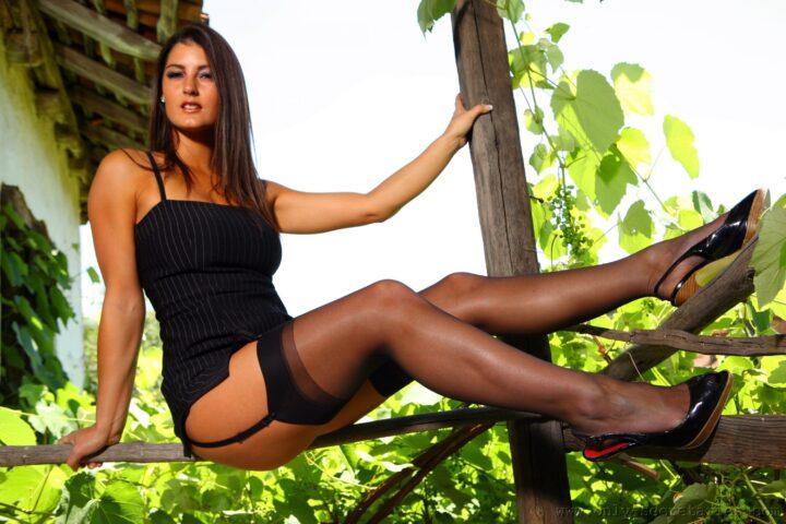 Сексуальная девушка с длинными ногами сидит на веранде.