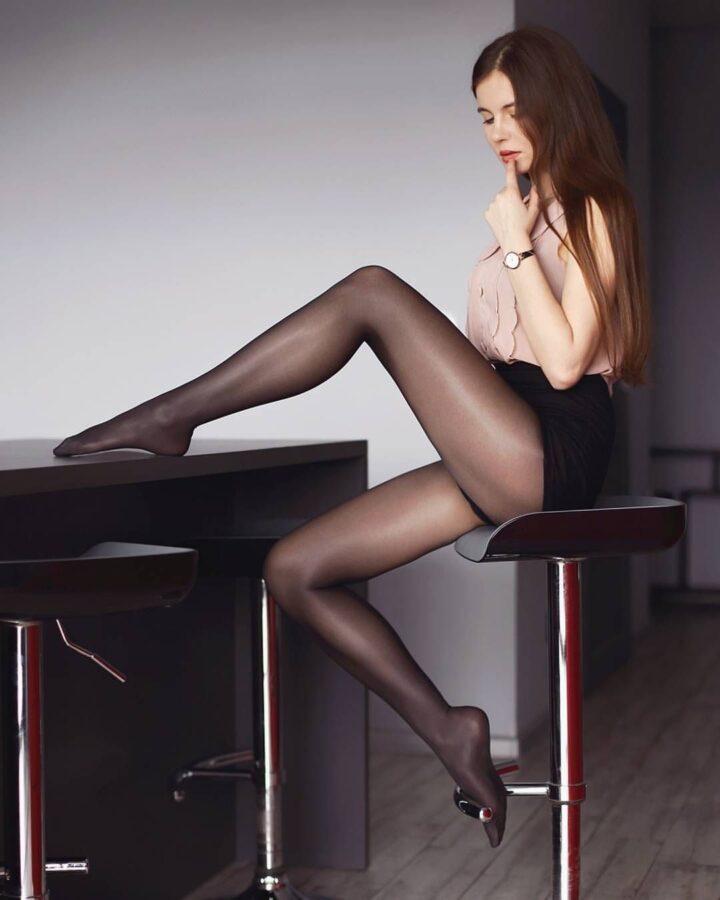Девушка длинноногая в черных колготках положила ногу на стол.