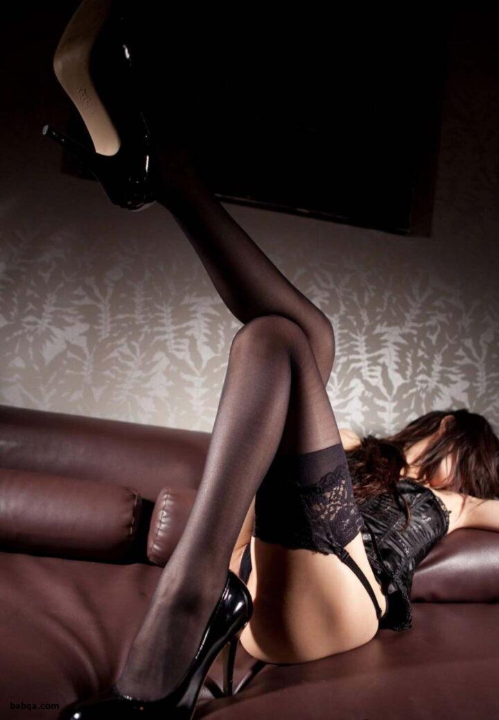 Сексуальная длинноногая брюнетка в черных чулках лежит на кожаном диване.
