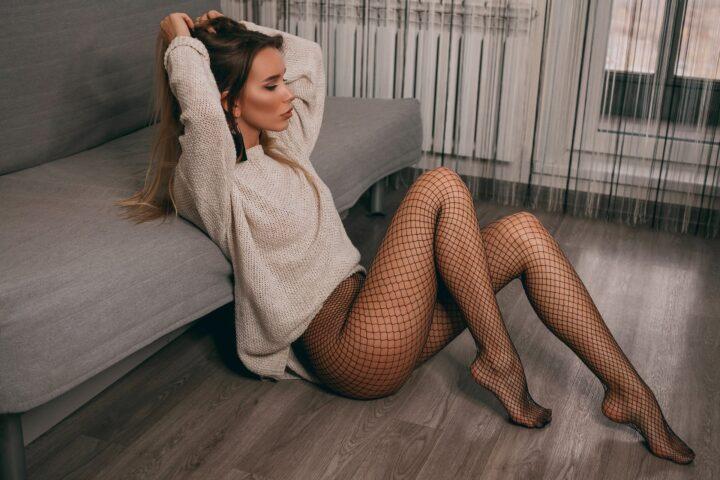 Красотка сидит на полу в кофте и колготках сетке без трусиков.