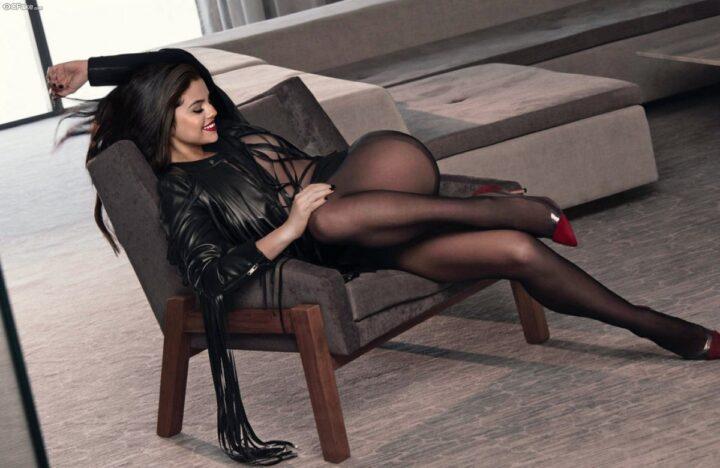 Девушка в кожаной куртке и колготках лежит на кресле.