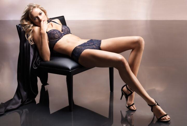 Блондинка с прекрасной фигурой в черном кружевном белье со стройными ножками.