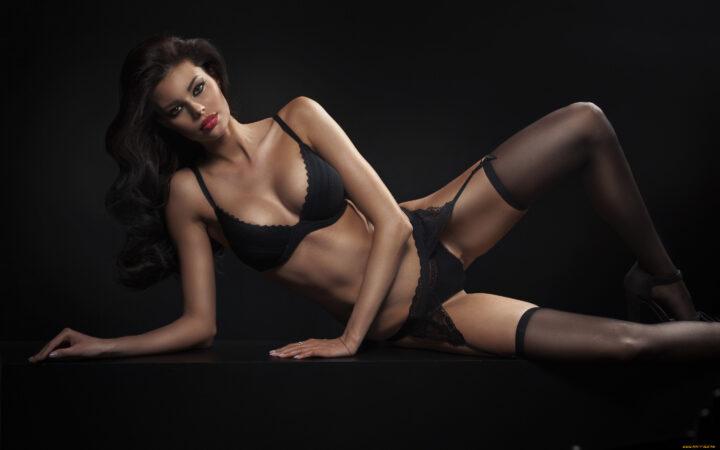 Роковая красотка в черном белье и черных чулках.