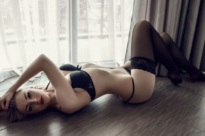Девушка блондинка с тонкой талией и круглой попкой лежит на полу у окна.
